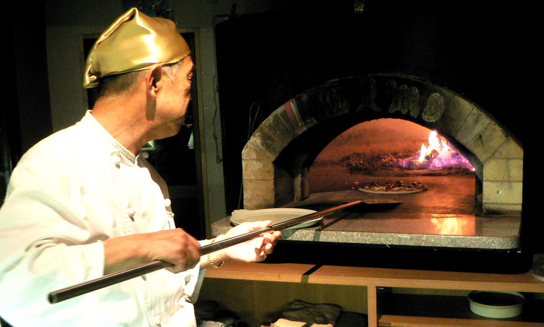 那須高原イタリアンのカフェロルモのピザ窯でピザを焼くオーナー
